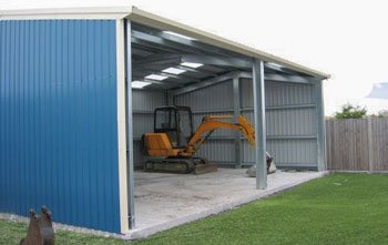 Rural farm shed with open front and mini excavator parked inside